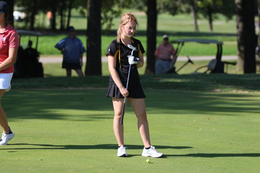 Senior+Erika+Rogers+prepares+to+put+the+ball+into+the+hole+in+a+JV+tournament+