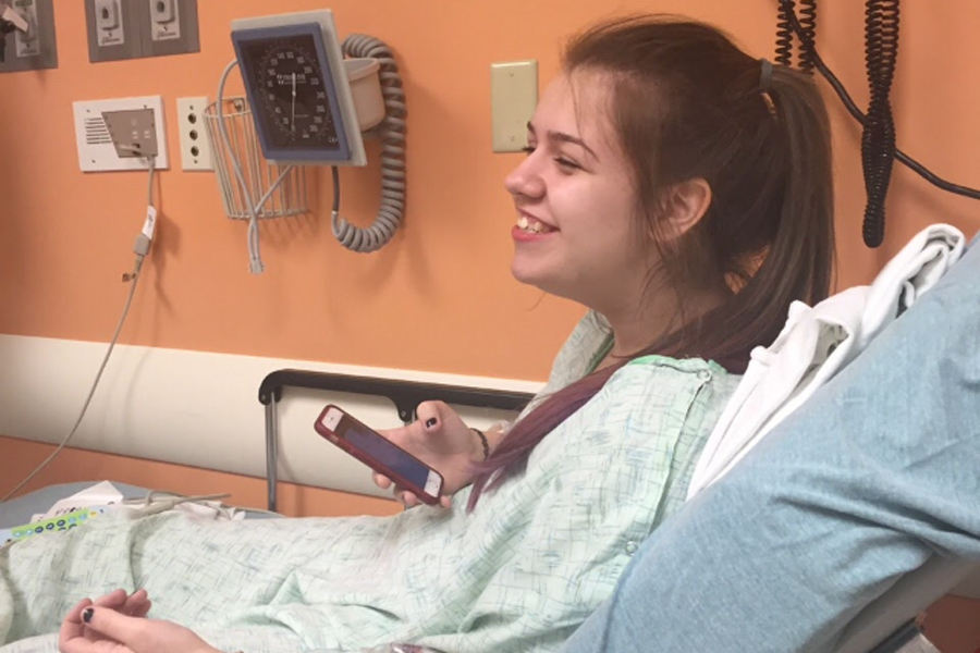 Junior Kailey Cripps sits in the hospital, smiling, while playing on her phone.