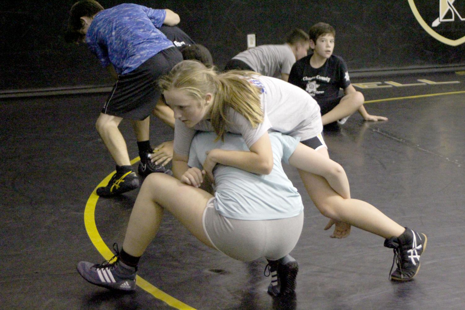 Freshman Nikki McIntosh and Abbie Carpenter spar during wrestling tryouts.