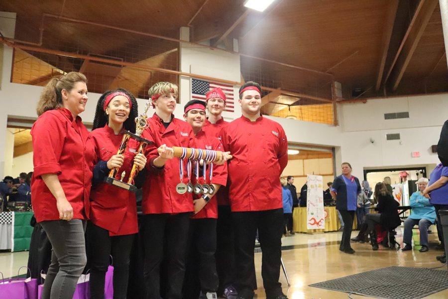 Senior Brendan Medlin holds the victory rolling pin with his Iron Chef team after their first place win.