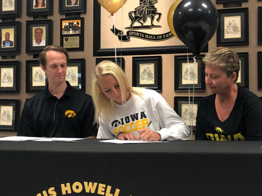 Senior Sam Cary signs a paper to commit to the University of Iowa.