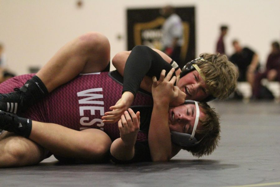 Sophomore Jesse Collins holds down a St. Charles West wrestler in an attempt to pin him.