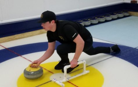 Senior Colin St. Aubin prepares to release the curling stone during a practice meet.