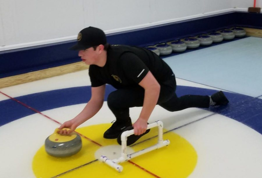 Senior+Colin+St.+Aubin+prepares+to+release+the+curling+stone+during+a+practice+meet.