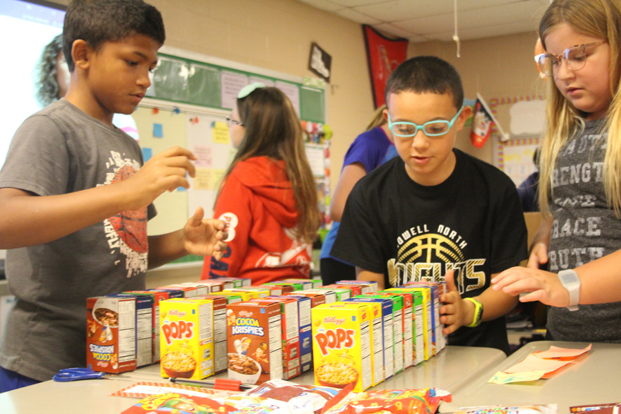 Students in Heather Bitter's fifth grade class count the number of boxes of cereal available for that week.  Every Thursday they put together bags for students in need of food on the weekend.