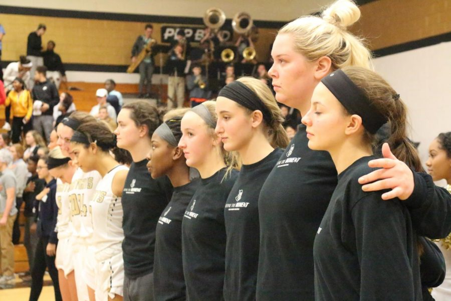 Junior Jenna Thompson (far right) and the girls basketball team stand in line during the National Anthem