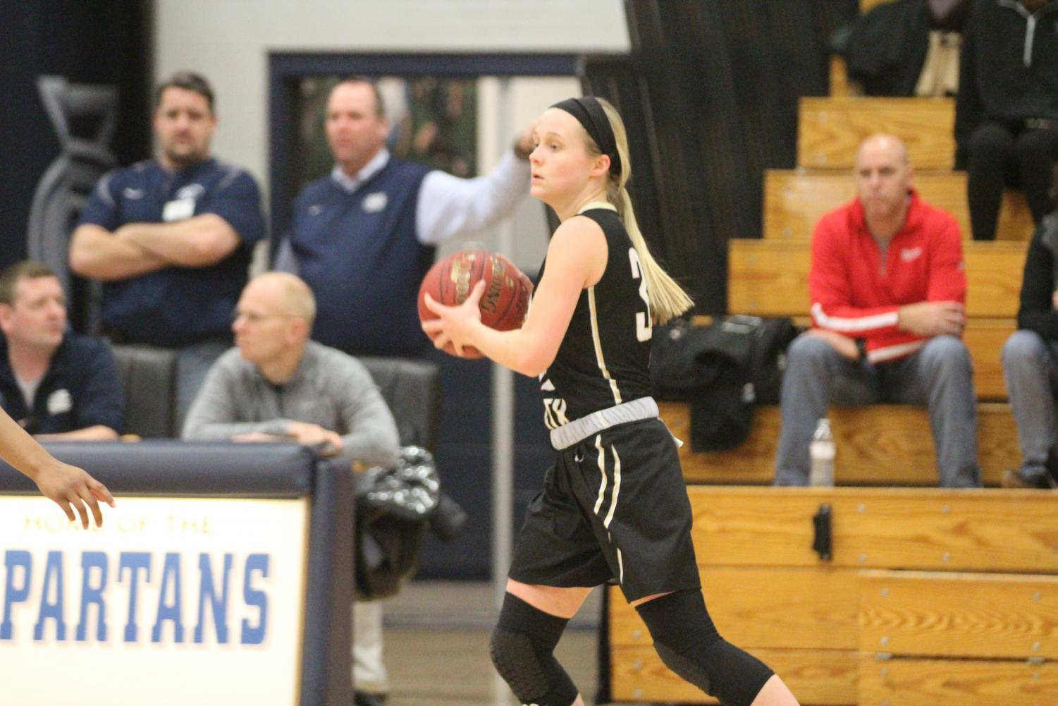Senior Maddie Stock prepares to pass the ball to one of her teammates in a game against FHC.