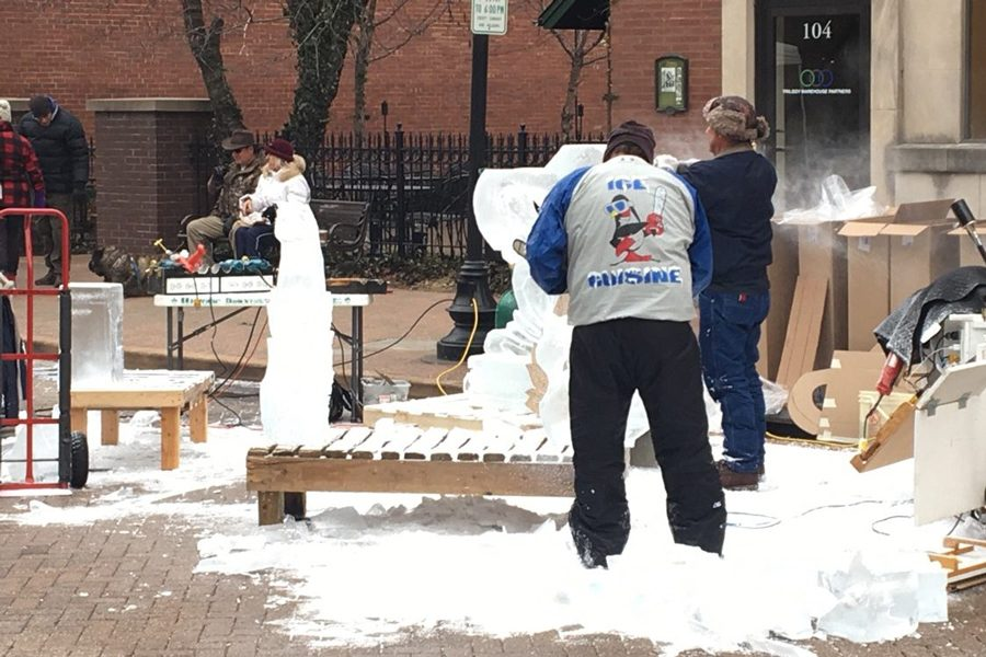 Carvers carefully work to shape the ice into the unique design sculpture to show to the crowd.