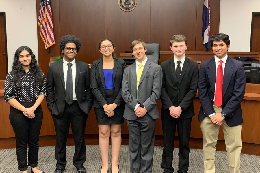 The FHN Mock Trial team stands for a group photo, in front of a judge's bench, after a successful meet.