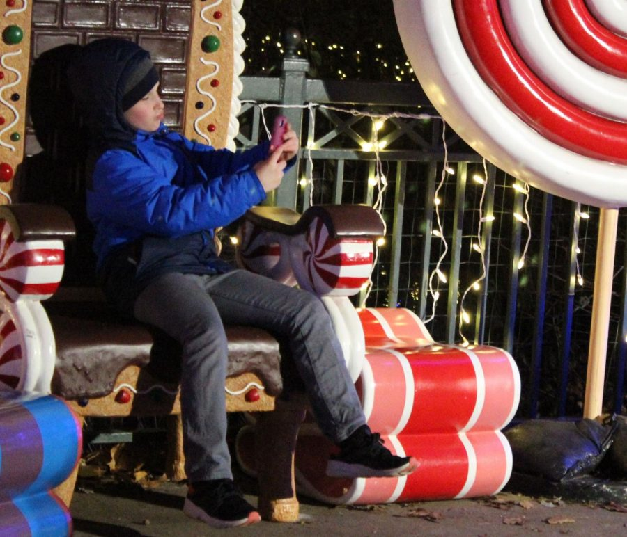 A little boy bundled up in his winter attire takes a selfie on his mother's phone as he sits on the gingerbread inspired chair. This is one of the many locations where families can take group photos or rest in front of the lake.
