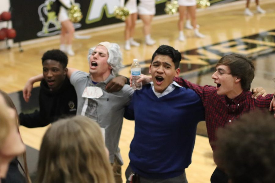Seniors Josh Simmons, Dillon Lauer, Noe Bustos and Adam Shine link arms and sway side to side to get the crowd to cheer along with them during the first girls' varsity basketball game on Dec. 7. The Goonies began holding meetings this year to help increase attendance and spirit at winter sports games.