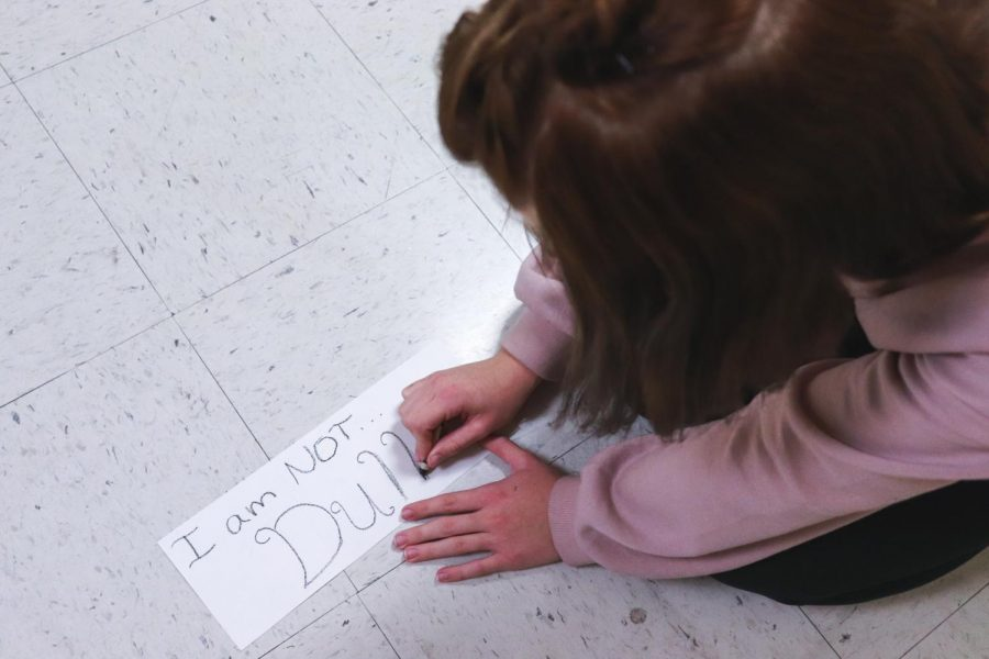 In her Intro to Art class, senior Erin Maniscalco writes I am not dull for her I am, I am not project.