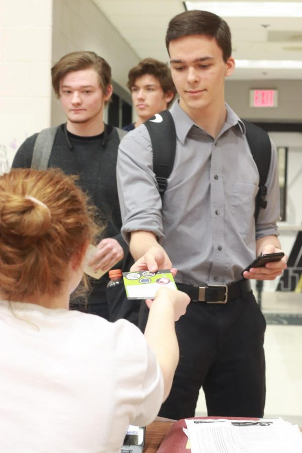 Senior Brandon Brophy hands in his permission slip to senior Autumn Schrader to sign into the blood drive. Students were given passes that determined the time that they would get their blood drawn. This was done so there wouldn't be a large line of students waiting. Normally blood drives have around 26 students and teachers donate but this year FHN had 159.