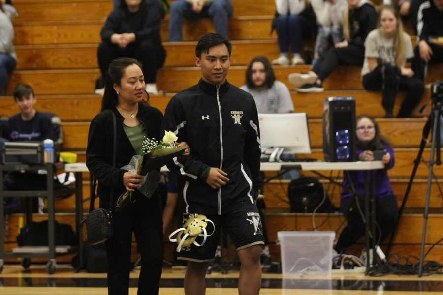 Senior Thadeus Meneses walks with his mother as he Is honored by his team during senior night on 1/15.