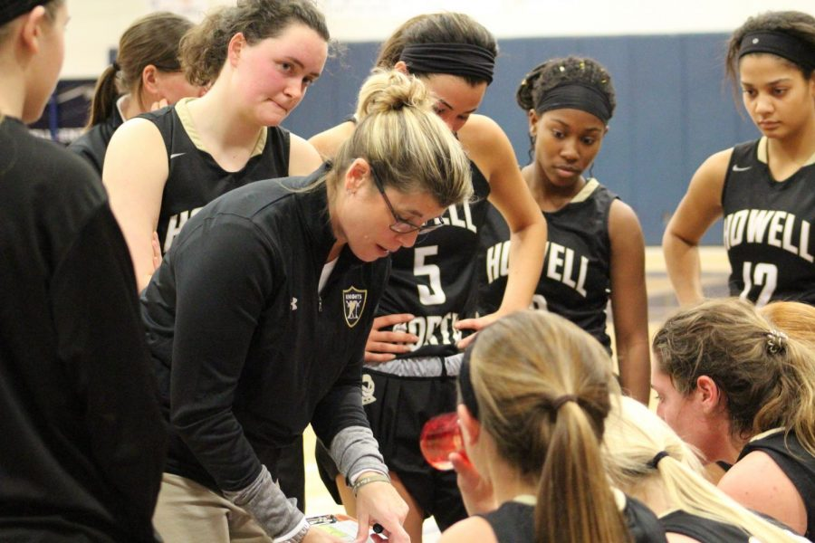 Coach Dawn Hahn discusses strategy with the girls team during a game against FHC. The Spartans would win the game 58-25.