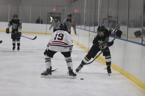 Freshman Derek Archer passes the puck up the boards. As a freshman it was Archer