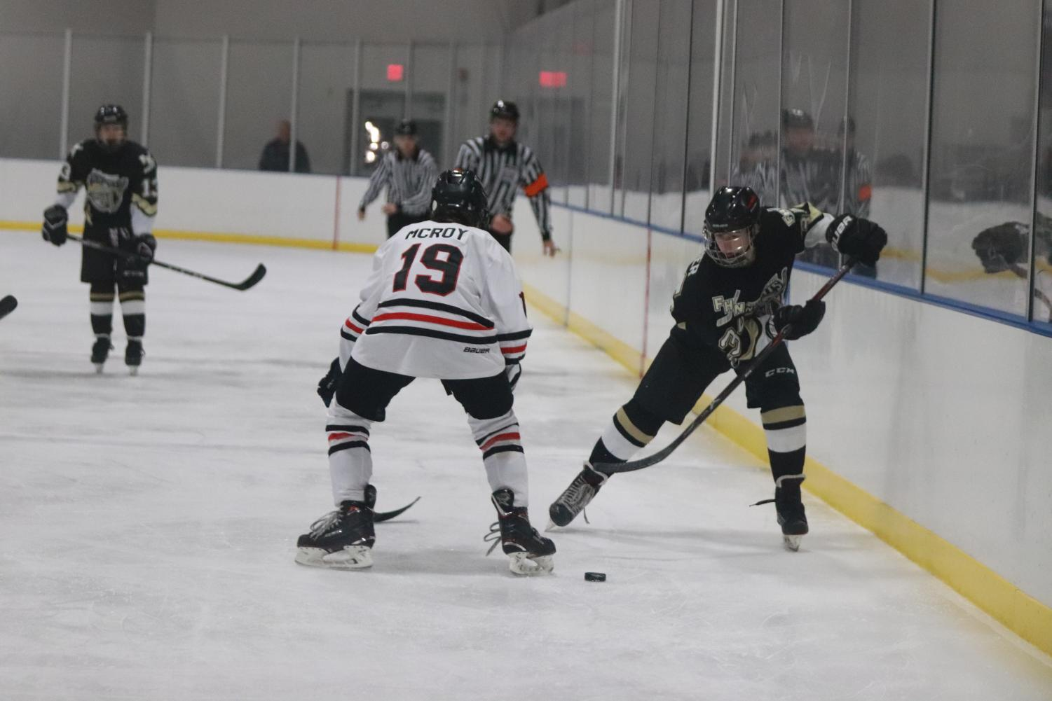 Freshman Derek Archer passes the puck up the boards. As a freshman it was Archer's first year on the team. Archer played center for the Knights this season.