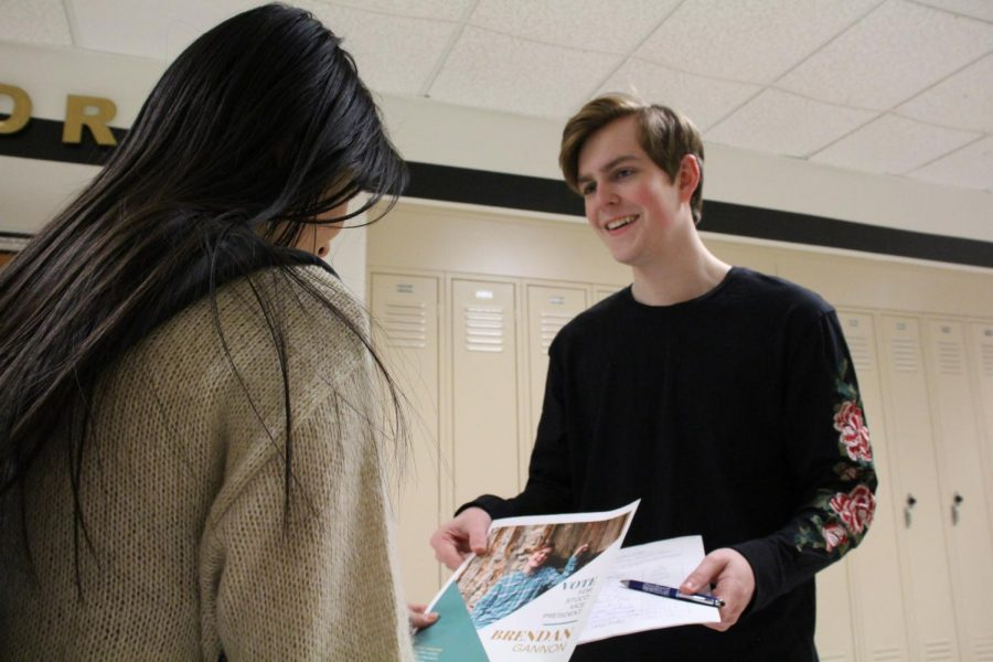 Brendan Gannon hands a student a flyer for the upcoming STUCO elections. Gannon wanted to become vice president instead of becoming president a second year. Every year, returning StuCo members are allowed to run to be an officer the following year.