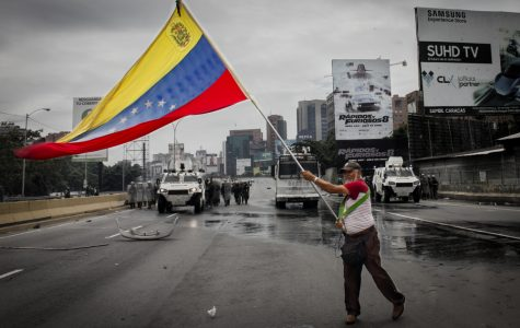 CARACAS, VENEZUELA - MAY 3, 2017: Protest in Caracas, Venezuela. Deputy of the National Assembly holds a Venezuelan flag when the protest is repressed by the Bolivarian National Guard with tear gas. - Image