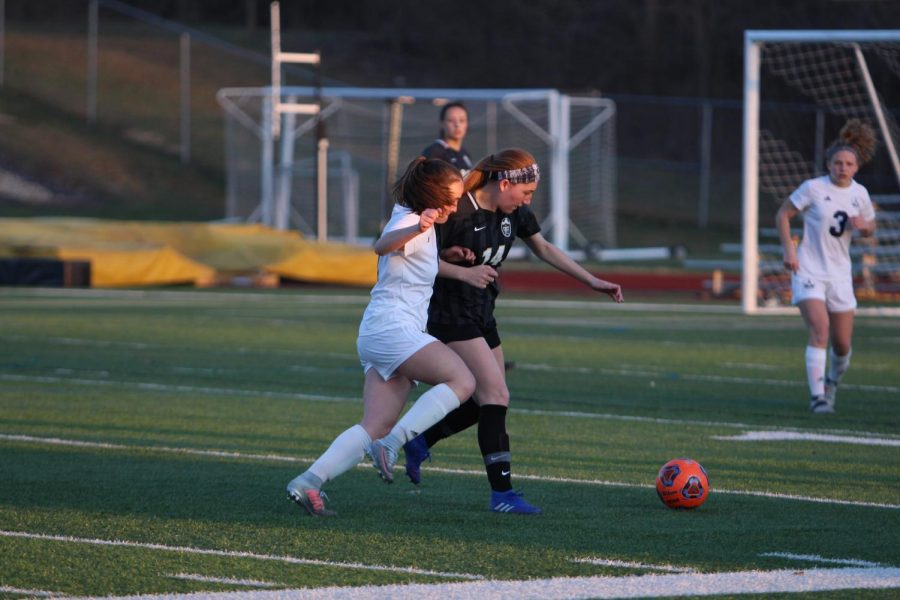 Senior Megan Crain fights with an FHC player for possession of the soccer ball.
