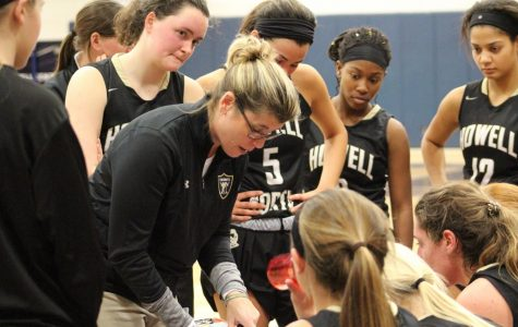 Head Coach Dawn Hahn speaks with her Varsity basketball players during a break in the game.