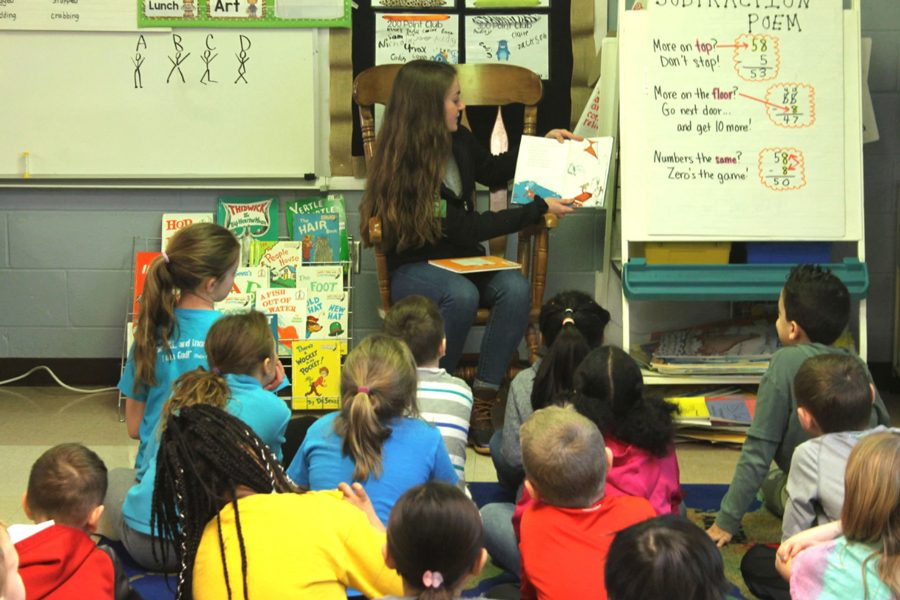 At+Henderson+Elementary+in+Mrs.+Hackman%27s+second+grade+class%2C+senior+Kelly+Burris+reads+to+the+students+on+March+1.+After+class%2C+students+did+many+Dr.+Seuss+activities+in+their+classrooms.+NHS+participants+picked+their+favorite+Dr.+Seuss+book+to+read+to+the+classes.+The+teachers+and+staff+were+very+excited+to+show+that+even+the+high+schoolers+from+FHN+find+reading+fun.+%E2%80%9DThese+books+are+timeless+and+even+enjoyable+for+the+older+kids%2C%E2%80%9D+Henderson+Elementary+librarian%2C+Emily+Gillet+said.