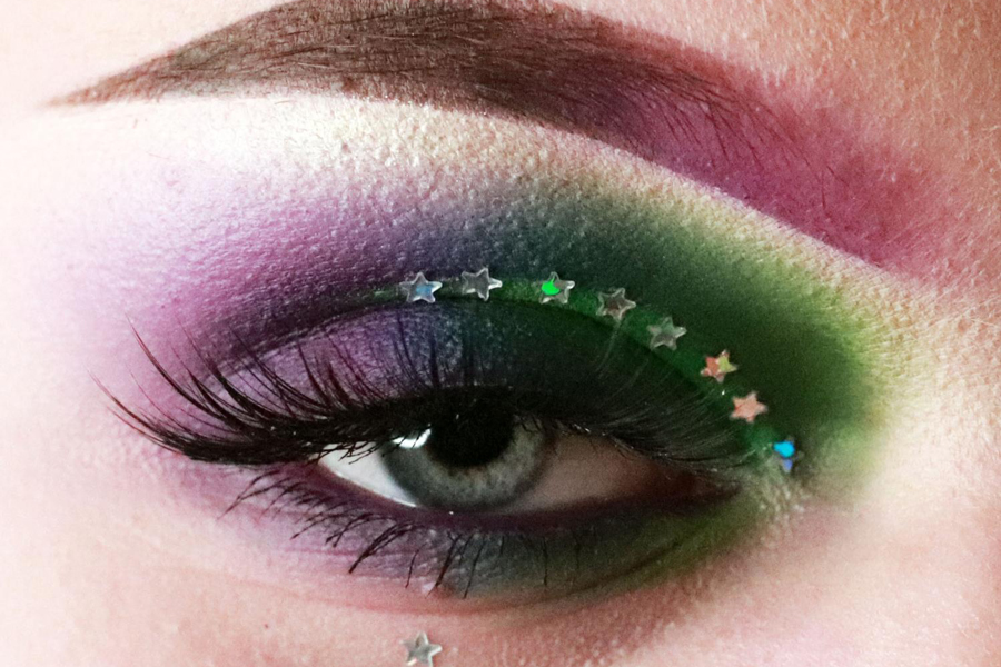 18-year-old Evelyn Moeckel models her Mardi Gras eye makeup. Moeckel is a self-taught makeup artist who specializes in eye makeup. She works at Sephora Beauty which requires her to do fun makeup to inspire her clientele. Moeckel strives to go above and beyond with new designs.
