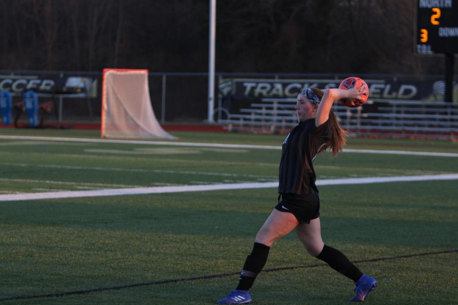 Senior+Megan+Crain+throws+the+soccer+ball+back+into+the+field+of+play.