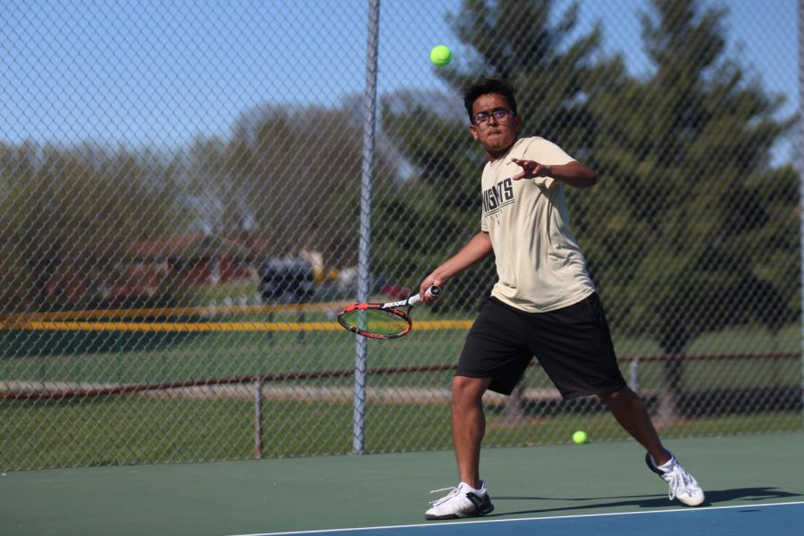 Senior Kanish Patel attempts to het the ball back over the net.