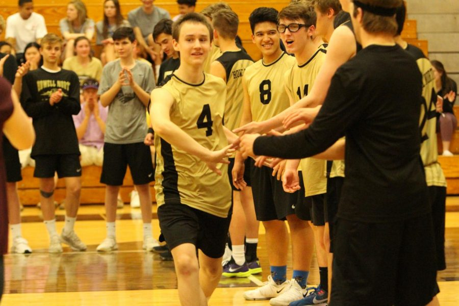 Freshman Zach Zimmerman runs down the line to get high fives from all his teammates before the game against De Smet.