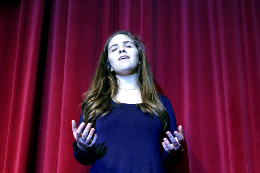 Sophomore Zoë Meier sings on the auditorium stage during her rehearsal for State Choir competition. Meier has been attending singing lessons since she was 12 and has been involved in musical theater since she was 8. She plans on continuing singing as a career in the future.
