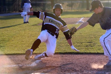 Senior Hunter Tabor attempts to avoid the tag from the pitcher and score