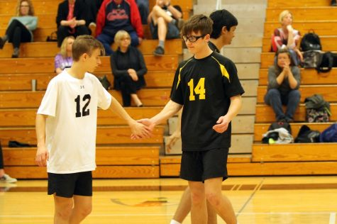 Junior Louis Primeau and Sophomore Peter Moxeley high five after gaining a point for the team.