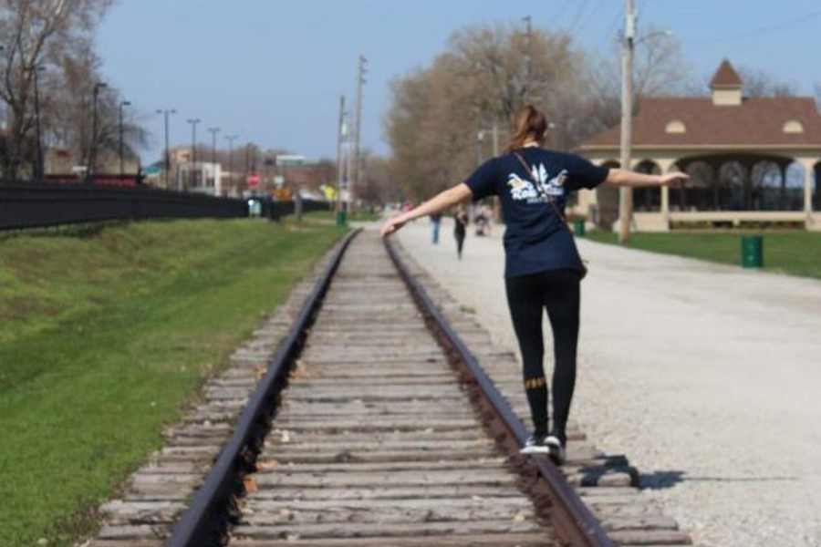 Walking on railroad tracks, junior Isabel Bira holds out her arms to balance herself. Main Street is a common area for people to get food and shop for knick knacks. It is located by the river and has small shops lining the streets.