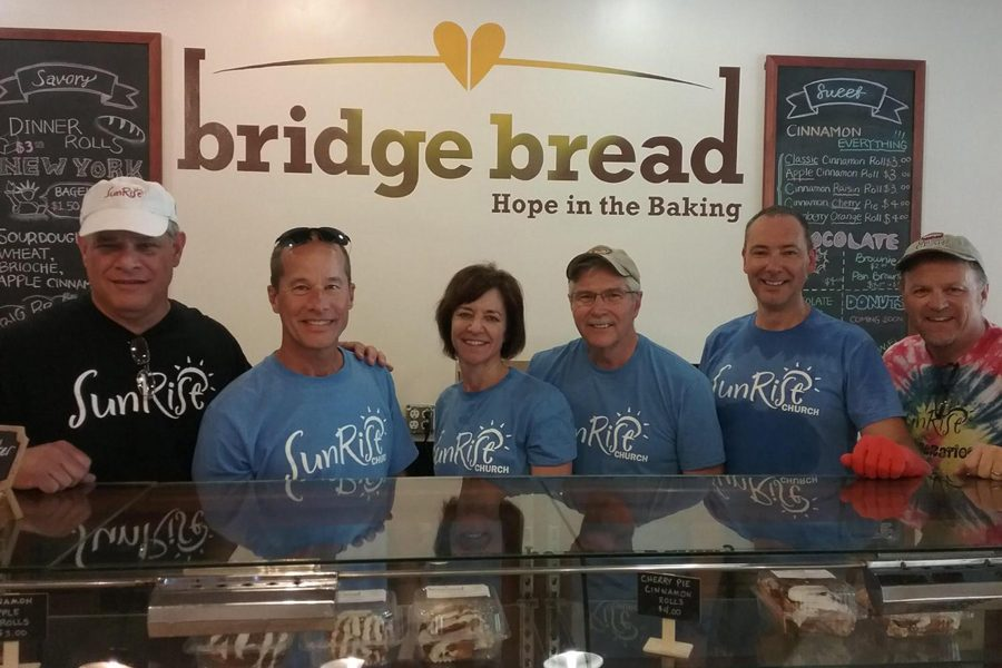 The+owners+of+Bridge+Bread+stand+in+a+line+behind+the+counter+as+they+pose+for+a+picture.+Bridge+Bread+is+an+organization+that+feeds+the+homeless+and+gives+them+jobs.+They+bake+bread%2C+bagels%2C+cake+and+brownies+daily.
