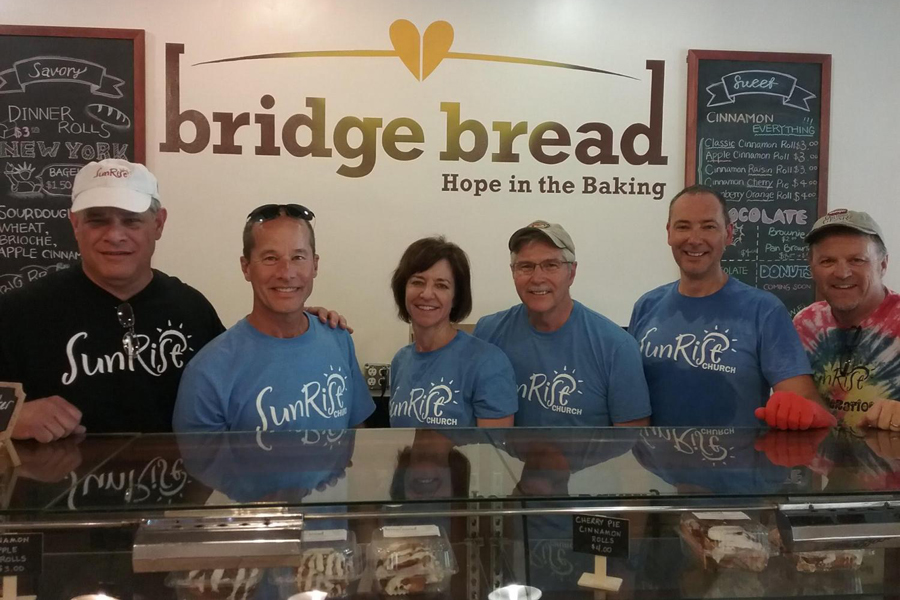 The owners of Bridge Bread stand in a line behind the counter as they pose for a picture. Bridge Bread is an organization that feeds the homeless and gives them jobs. They bake bread, bagels, cake and brownies daily.