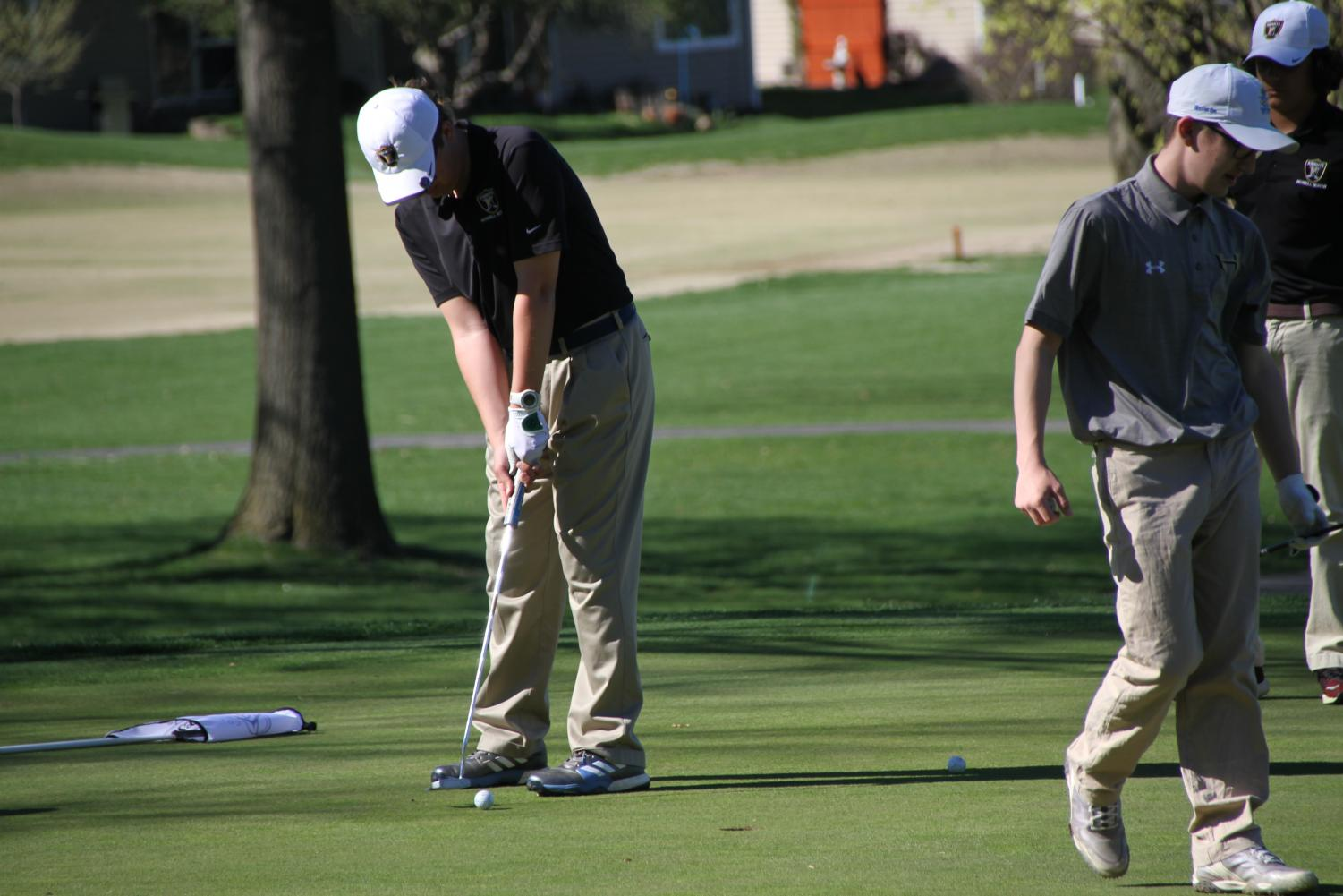 A Knight golfer putts a ball on the green in a competition.