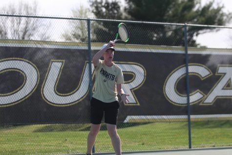 Sophomore Ben Ell swings his racket as he hits the ball.