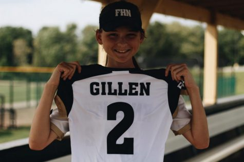 "On the FHN's softball field Jessica Gillen holds up her jersey for varsity on Sept. 21 to show her number. Gillen has been playing softball almost all her life, since she was five years old her parents would put her into little leagues. So she just decided to continue with softball and has loved it ever since.  ""My parents wanted me to be active as a kid,"" Gillen said."