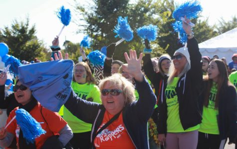 Participants in the crowd at the Autism Speaks Walk cheer for a guest speaker. The event had multiple guest speakers including Fox 2 New co-anchor Margie Ellisor. The event also had multiple organizations that donated money for autism research.