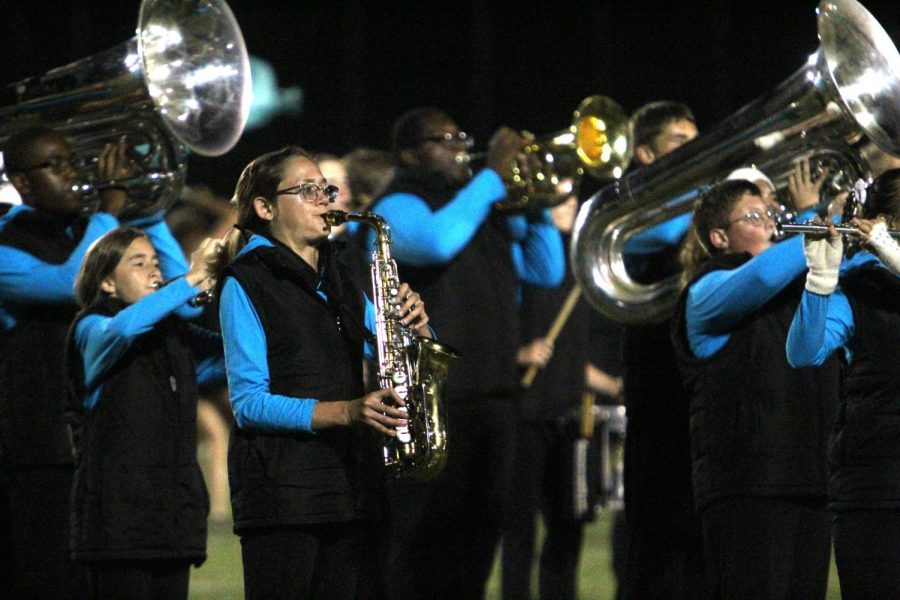 "At the football game on Sept. 6, sophomore Rylie Miller plays the alto saxophone in Knightpride's new marching band show, ""Freeze."" This is Miller's second show with the band. ""I enjoy experiencing band memories with my friends,"" Miller said. (Photo by Avery Witherbee)"