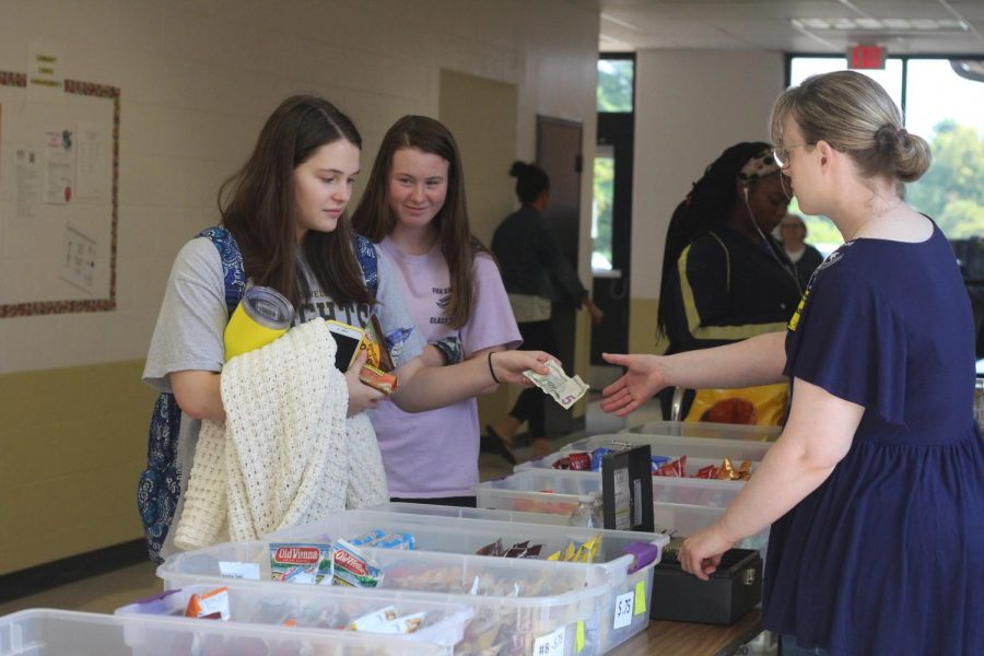 At the snack table, junior Brandi Stover hands money to a parent volunteer. The snack table has a variety of snacks for students and staff members to choose from. The money collected will go towards the Senior All-Knighter. (Photo by Allie Moore)