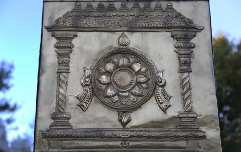 A sudarshana chakra pressed into brass rests on the pillar standing outside the temple. The symbol, whose name translates to