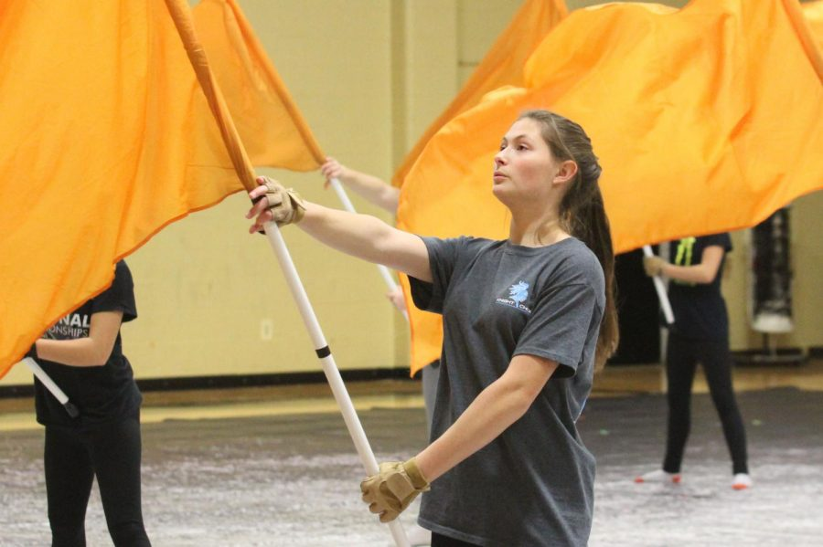 Standing tall, junior Lily Karase holds out her flag preparing to spin it during winter guard practice. Many new changes occurred this year, such as there is only one team, getting rid of the division between JV and Varsity. Two returning coaches are preparing the show this year. (Photo by Avery Witherbee)