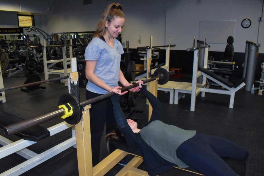 On Feb. 21, freshman Maddie Swart spots sophomore Sydnee Williams in FHN's weight room to build up strength in preparation for girls' lacrosse season. Both athletes have at least three years of experience, and have been putting a lot of time and effort into their sport specific skills and pre-season workouts.