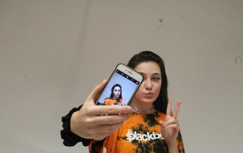 Sophomore Natalie Stevens poses in front of a phone.