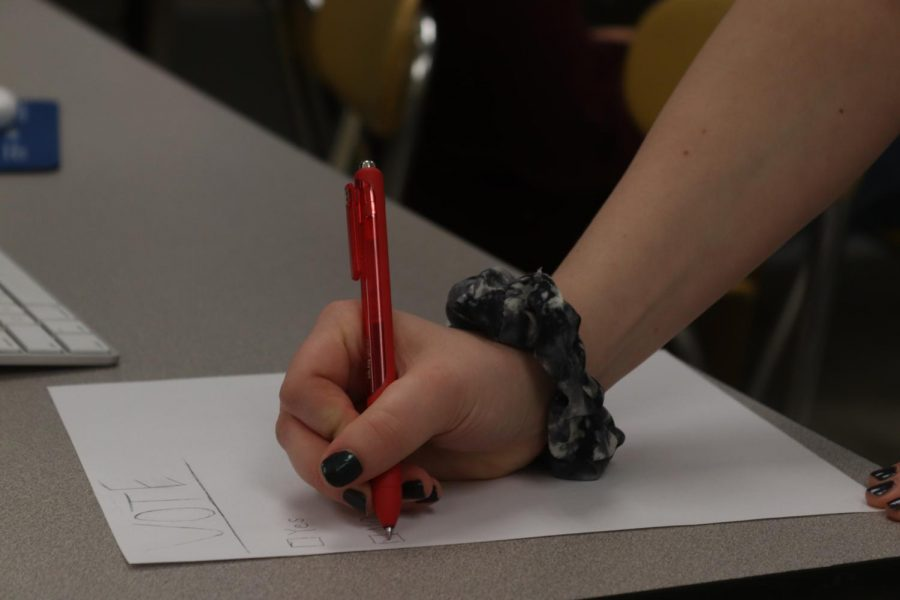 A student checks no on a piece of paper they recieved from a class mate. The school board is going sworn in new members in April. The board only has three available spots.