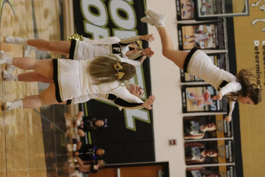 Senior Lindsey Papka is thrown into the air in the cheer performance during halftime.