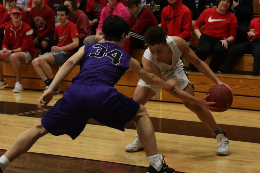 Senior Cameron Lewis looks to pass the ball while trying to avoid the opponent from stealing it away.