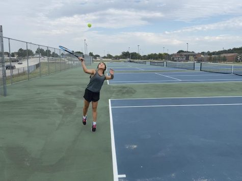 Senior Iris Lee serves the tennis ball during practice.